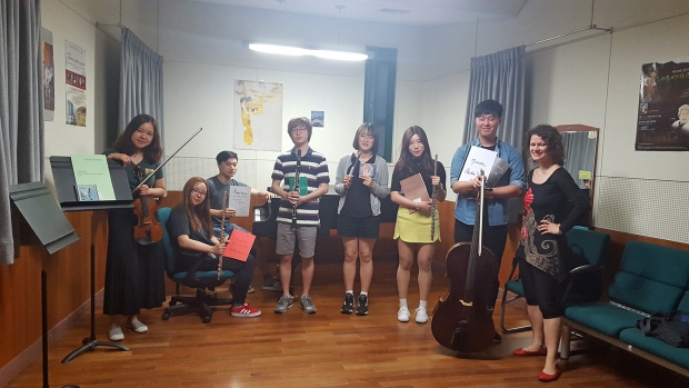 German School of Music violin professor Viktoria Kaunzner poses with students and presents a donation of music from Romanian composer Violeta Dinescu to be added to the GSM library. (Photo: Chun Min Ji)